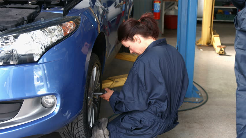 Female mechanic working on a tire in the garage