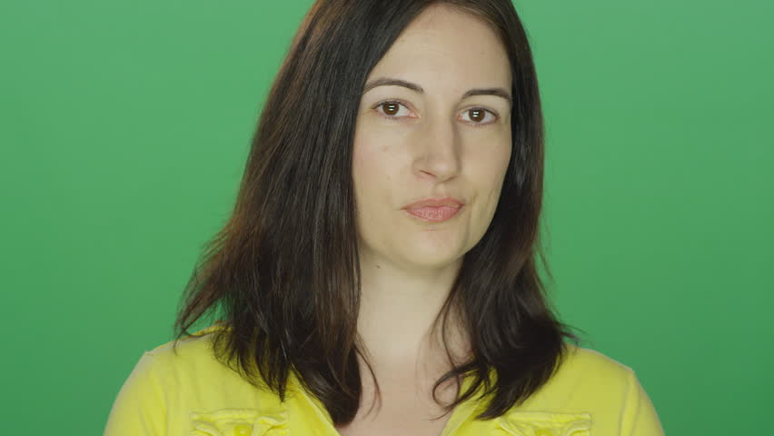 Young brunette woman casually flirts and smiles, on a green screen studio background | Shutterstock HD Video #14905405