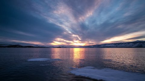 Sunset on freeze ice of the Baikal lake. Slow camera motion by slider. Time lapse