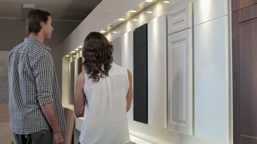 Couple Browsing Samples Of Cabinets Cupboards In Modern Kitchen Showroom  Home Remodeling, Renovation And Makeover