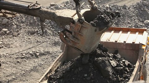 Huge electric shovel loads iron ore onto a truck at mine,  industrial exterior, ore mining quarry, sunny day, summer, mining of iron