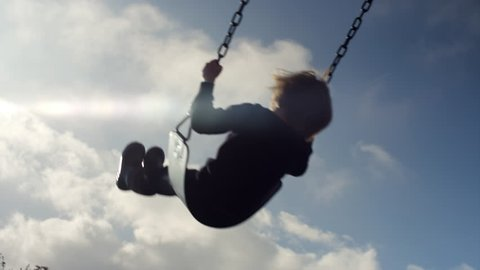 A little girl swinging, slow motion, silhouette in the sky, lens flare