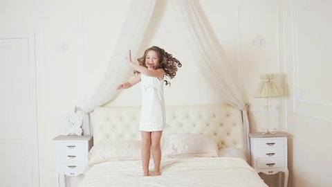 happy girl jumping and dancing on the bed