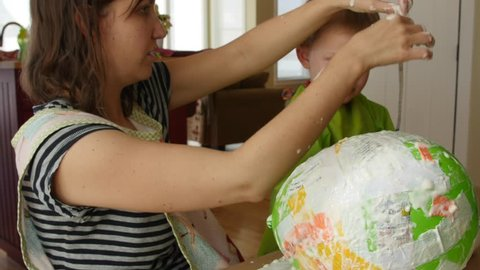 A mother and her boy make a piñata with a balloon, paper, and paste dolly shot