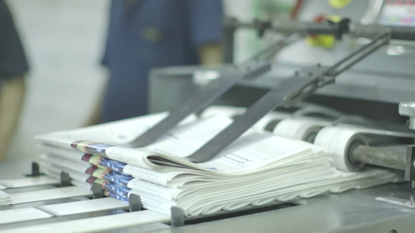 medium close up on newspapers being folded on a conveyor belt