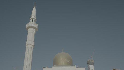 Mubarakia Mosque Kuwait. Worm's eye view of the elegant white minaret and golden dome of the Mubarakia mosque against a blue sky.