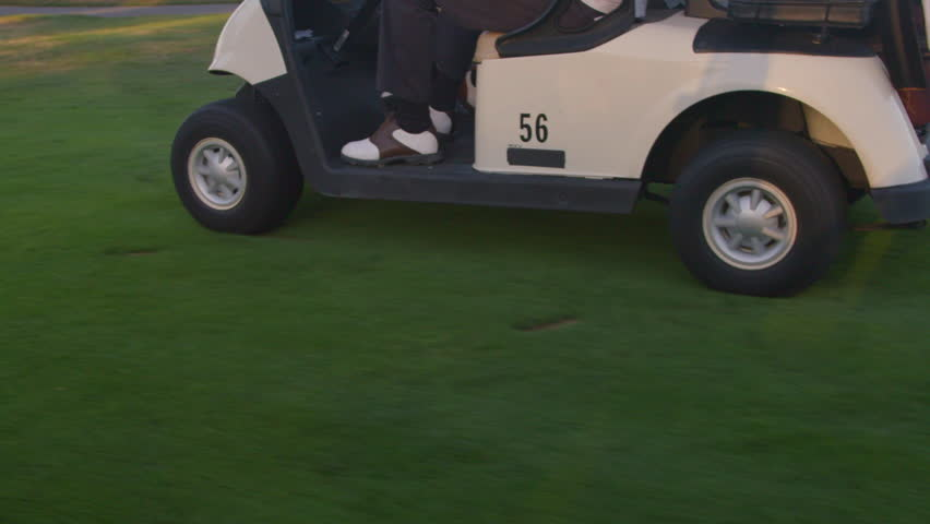 Beautiful shot of two golfers driving a golf cart on the fairway
