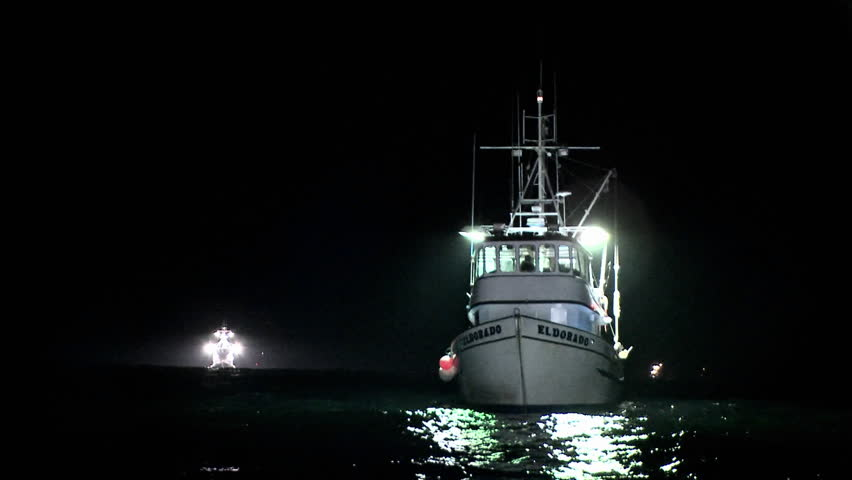 A boat sits rocking in the water at night.