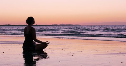 Silhouette young woman practicing yoga on the beach in fiji, pink sky sunset,  at sunset healthy life, new years resolution, healthy mind