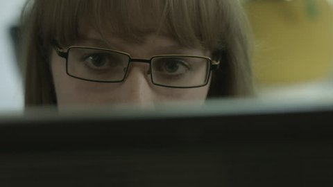 Ungraded: Girl with eyeglasses looks into the computer monitor. Sometimes she is distracted and talks to colleagues or visitors. Source: Blackmagic Prod.Cam.4K, ungraded ProRes from camera. (av23803u)