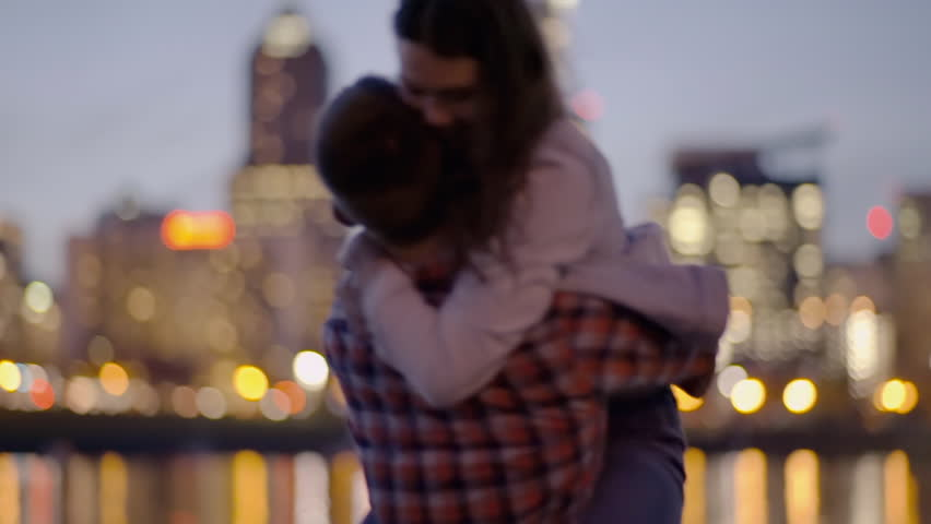 Playful Couple Dance On A Dock Across From City, Man Twirls His Girlfriend And Surprises Her With A Kiss On Her Hand, She Laughs
