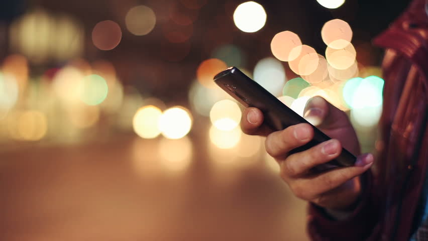 Man sms texting using app on smart phone at night in city. Close up