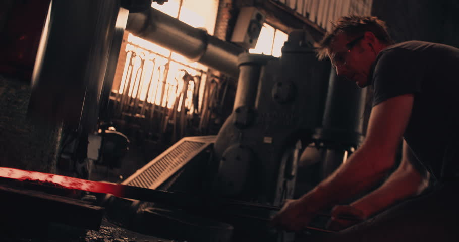 Manufacturing process of wrought iron. Blacksmith holding a piece of iron with tongs while a mechanical press is hammering | Shutterstock HD Video #15047575