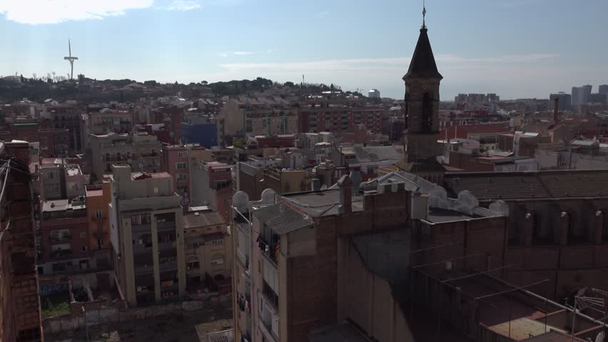 Peaked bell tower of Catholic church rise above city roofs, cityscape panorama. Panning camera shows Sant Angel Custodi basilica belfry, Hostafrancs area at Sants-Montjuic district of Barcelona city