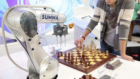 MOSCOW, OCTOBER 30, 2015: Visitors playing robot chess in game center