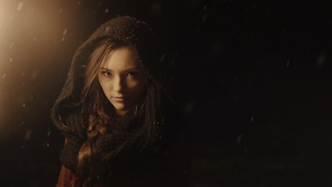 Portrait of a young mystic woman in the dark forest holding a torch. Woman with torch over dark night background. Falling snow. Slow motion.
