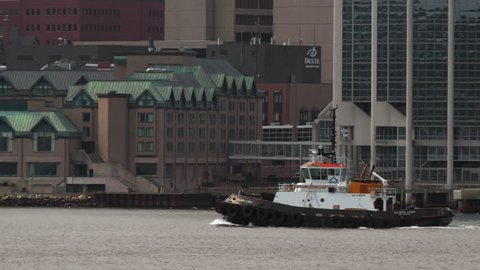 A Halifax towboat/tug boat as it makes its way from Dartmouth to Halifax going past the downtown of Halifax.