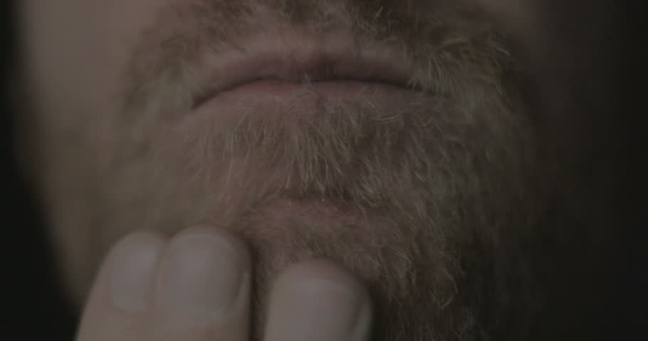 Static close up shallow depth of field rack focus shot of a man touching and rubbing his beard while thinking.