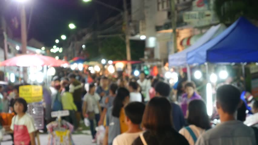 Defocused of tourists and locals walk among stalls at the famous walking street, Kad Kong Ta Street Market in Lampang Province. There are various things to buy and eat.