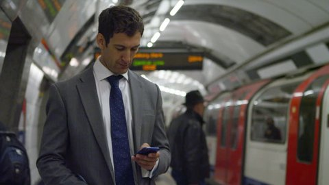 4k Businessman texting on smartphone whilst waiting for subway train