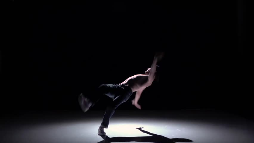 Dancer man with naked and denim torso starts dancing breakdance on black, shadow, slow motion