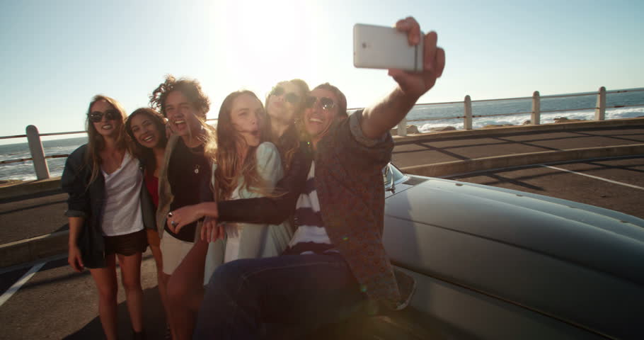 Group of multi-ethical teenager friends having fun by embracing and making funny faces taking a self portrait close to the beach