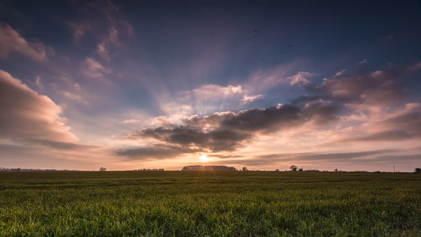 Sunset Time Lapse Clouds Moving Over Rolling Green Fields 4K