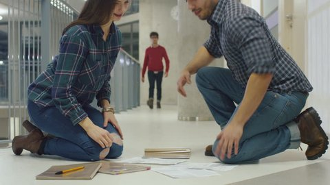 Young man helps a student by picking up her papers from the floor. They meet each other eyes and fall in love at first sight. Shot on RED Cinema Camera in 4K (UHD).