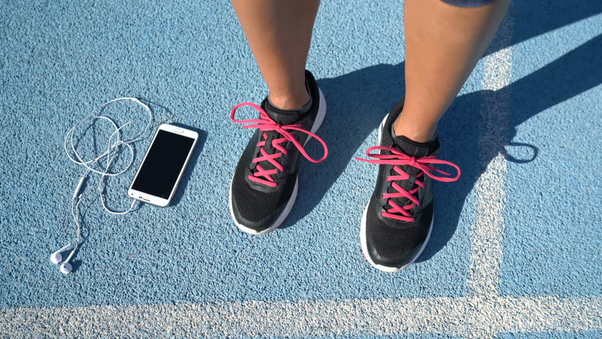 Closeup of running shoes next to smartphone on blue athletic track. Woman runner ready to run holding her phone and earphones for music motivation during cardio workout outdoors. #15186925