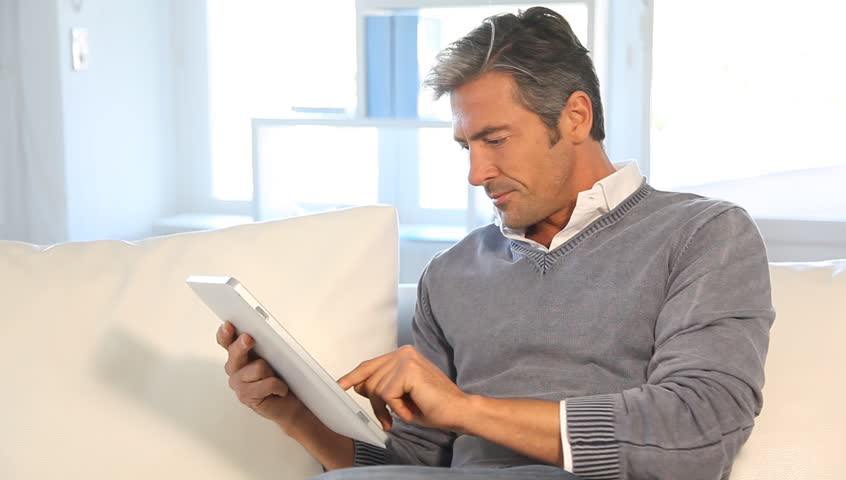 Man at home using electronic tablet