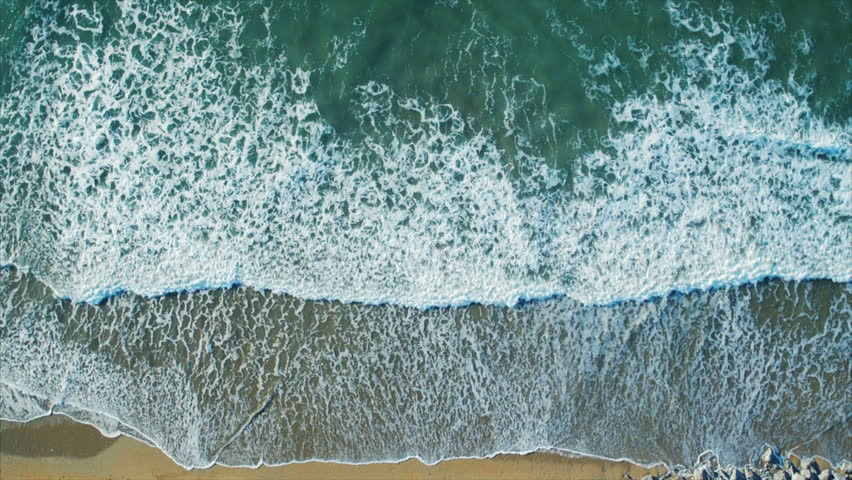 Aerial drone footage of serene sea waves reaching shore. Slow lockdown shot of textures being formed by white sea foam. As the waves calm the patterns change. Filmed from an overhead perspective.
