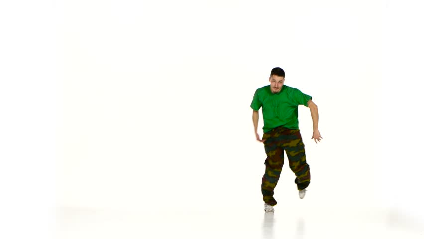 Talanted young dancer man in green shirt goes on dancing breakdance on white