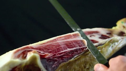 cutting iberian ham on traditional spanish style (handmade for tapas)