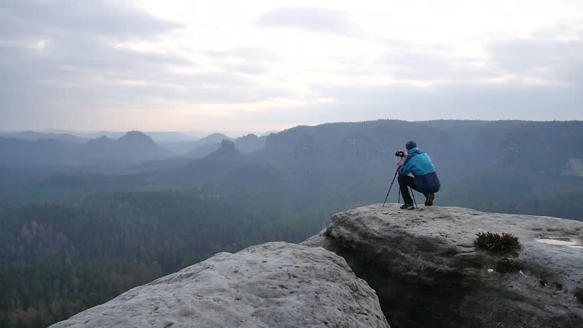Photographer in blue jacket at tripod  on rocky view point and taking photos of misty morning landscape. Hike in rocks. Melancholic autumn morning.  | Shutterstock HD Video #15267205