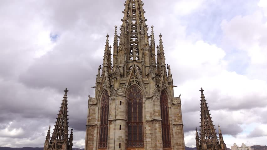 Spiked neo-Ghotic tower at top of Barcelona Cathedral, dolly shot, camera move backwards on church roof, showing detailed spire against cloudy sky. High decorated ancient structure