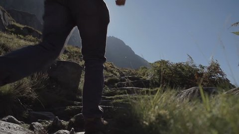 Hiker Walking In Snowdonia Wales. A shot of a tourist hiker walking up a mountain in Snowdonia Wales. Filmed on a perfect sunny day in North Wales in the United Kingdom.