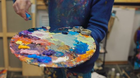 artist brush mix color oil painting on palette is holding in his hand closeup. In workshop