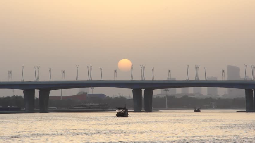 Dusk Arab sunset at Dubai Creek and Al Garhoud Bridge, sun disk disappear in horizon haze. Time lapse shot. Car traffic flow rush at road, telephoto lens view, few boats sail along harbour