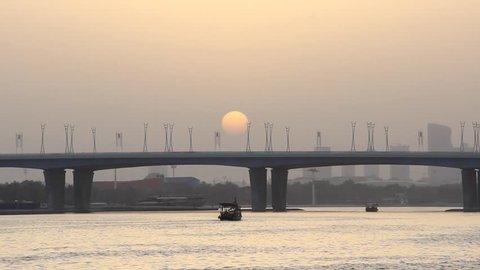 Dusk Arab sunset at Dubai Creek and Al Garhoud Bridge, sun disk disappear in horizon haze. Time lapse shot. Car traffic flow rush at road, telephoto lens view, few boats sail along harbour
