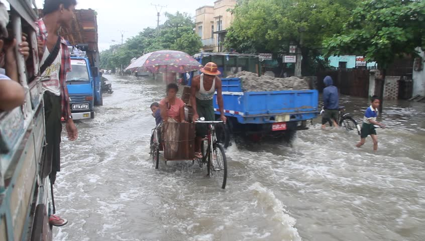 MANDALAY, MYANMAR - AUGUST  20: Vehicle and foot traffic on a flooded street circa August 20, 2011, Mandalay, Myanmar.