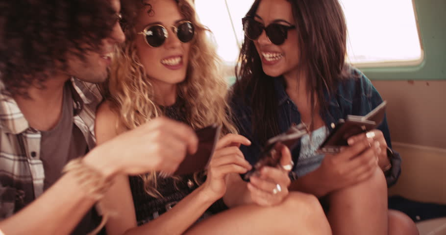 Hipster mixed race woman and hipster caucasian girl friend sitting together looking and laughing at polaroid pictures of road trip in back of retro van
