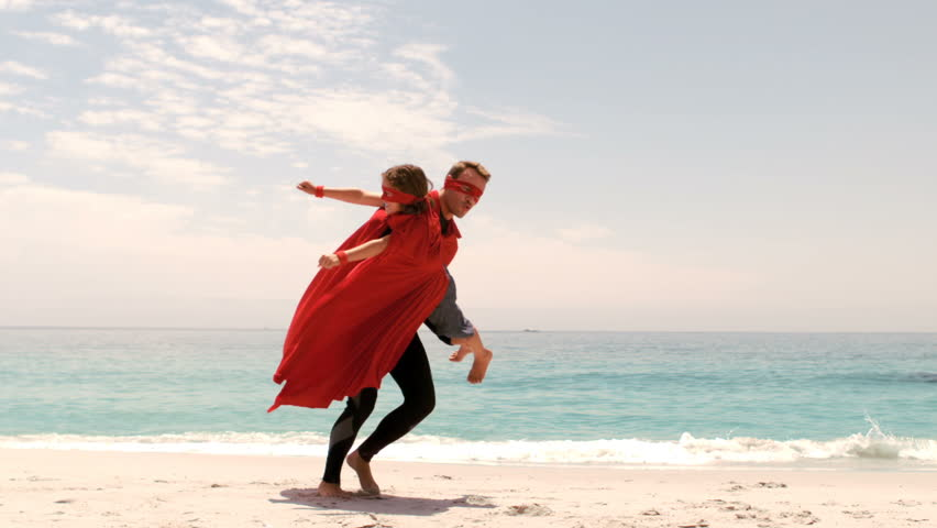 Father and son dressed as superman on the beach