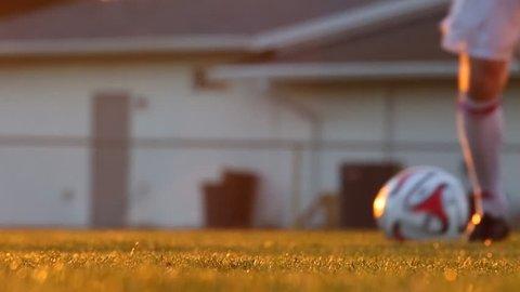 Slow motion shot of a soccer player kicking a ball at sunset / Orlando, Florida - USA., February, 2014