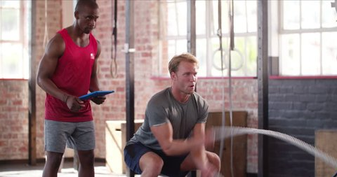 Young adult man doing crossfit workout with ropes led by his personal trainer with tablet
