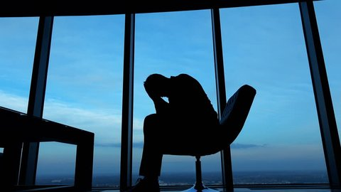 Silhouette of sad, unhappy businessman sitting on armchair by the window, against the sky, 4K
