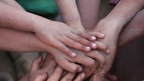 Many connecting poor children's hands. Mrauk-U, Myanmar