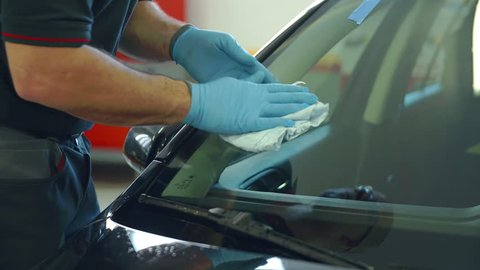 A worker in a car repair shop is cleaning the front window with a nice cloth after the mistake has been removed. He's also cleaning under windshield wipers. Close-up shot.