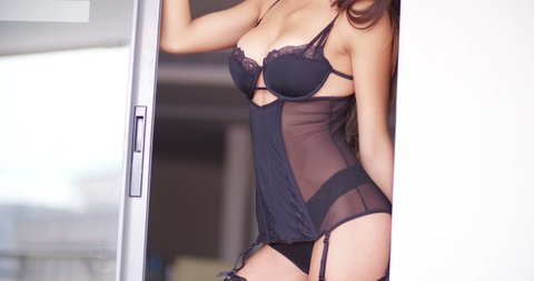 Sexy woman in lingerie and tights is standing in door
