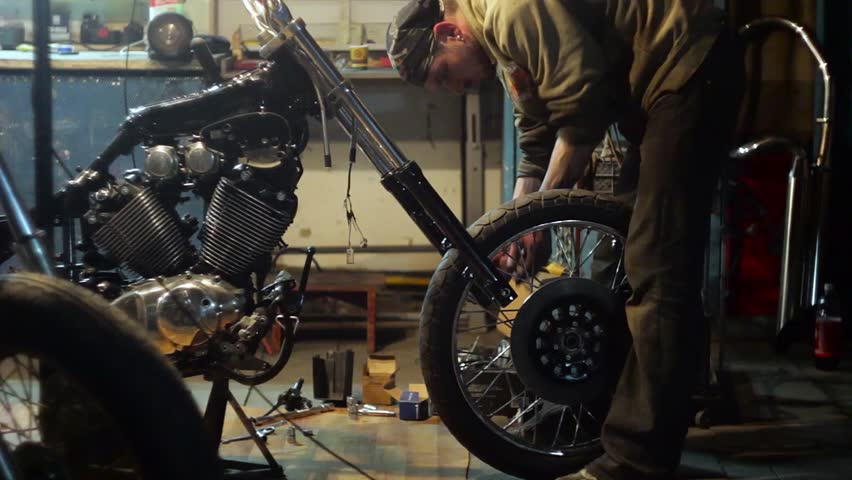 Auto mechanic assembles custom motorcycle in his workshop. Create an exclusive moto bike in the garage. | Shutterstock HD Video #15430015