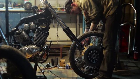 Auto mechanic assembles custom motorcycle in his workshop. Create an exclusive moto bike in the garage.